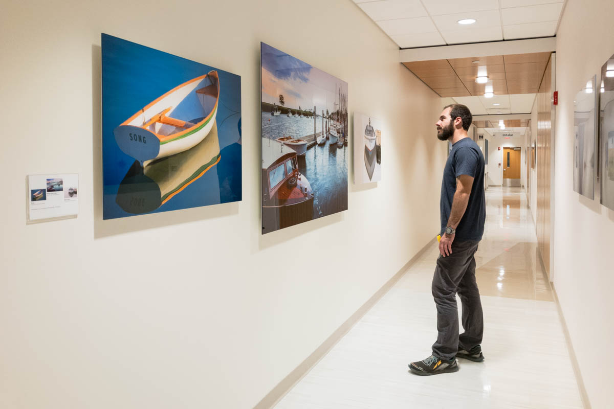 man standing in long hallway looking at a group of three large acrylic face-mounted prints