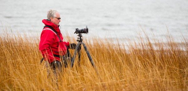 phil nelson standing in beach grass with camera and tripod