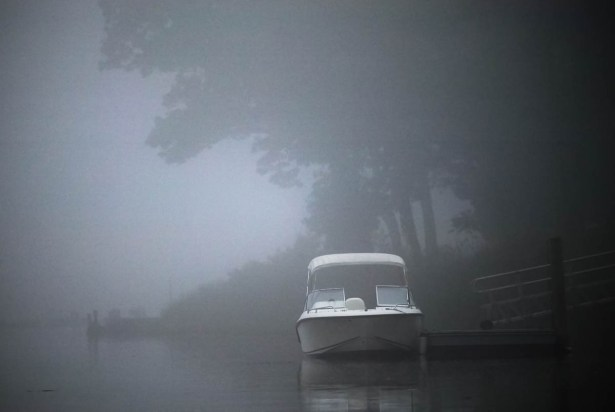 motor boat docked in fog on a river