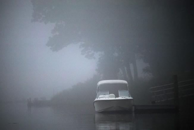 motor boat docked in fog on a river