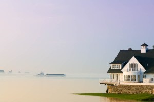 barge drifts passed house in morning mist
