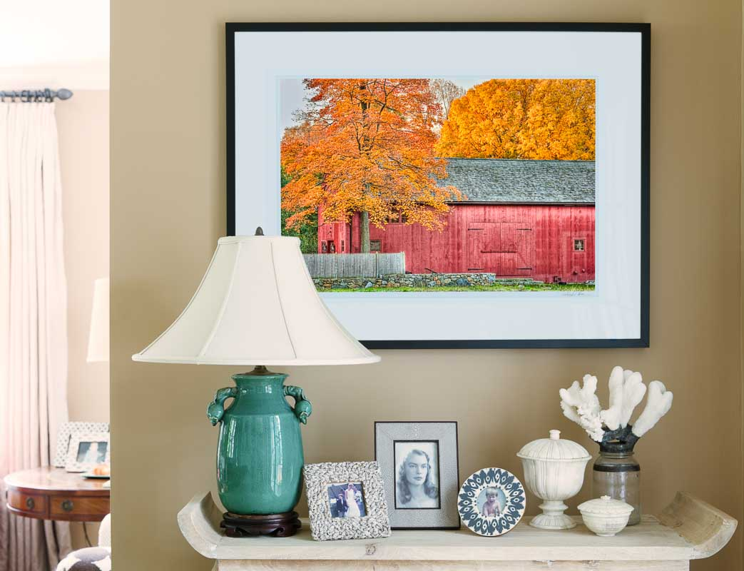 framed print of red barn on living room wall