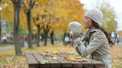 stock-footage-fall-woman-sitting-in-autumn-park-drinking-coffee-with-colorful-yellow-leaves-falling-from-trees