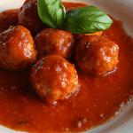 ITALIAN SAUSAGE MEATBALLS with tomato sauce and basil leaves