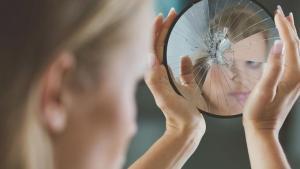 %name Woman holding small broken mirror