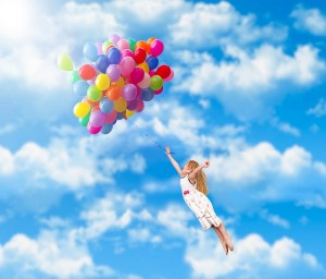 %name Child flies on the balloons. Blue sky, clouds. A little girl in a white dress