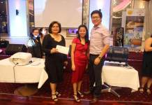 Patricia Gutierrez (left) and Micelim Geloso award the airfare prize to the lucky winner.