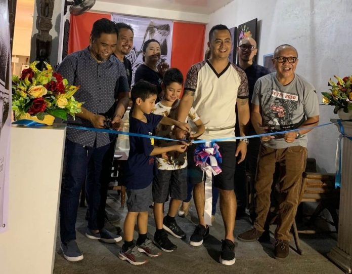 Ribbon cutting at the opening of Christian Bulos' art exhibit