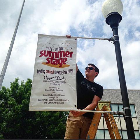Chris Luner, Summer Stage production manager, hanging up a banner