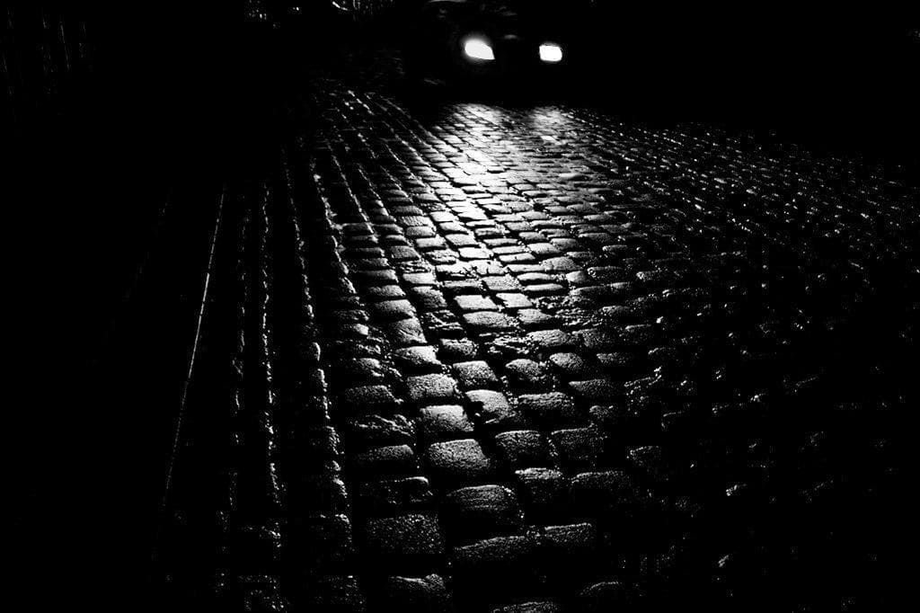 image of cobbled street with car lights