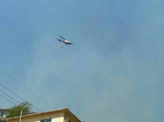 A helicopter flies overhead, bringing water, supplies. Emergency vehicles swarmed to the scene all day and night.