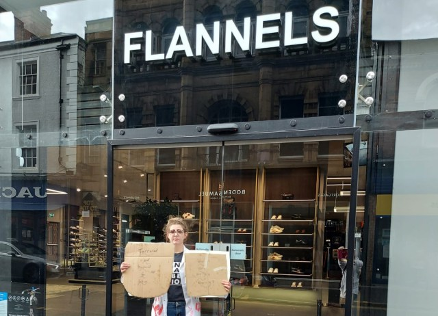 A lone protester holds two placards outside Flannels