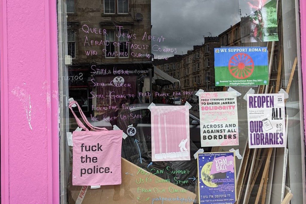 """Window of Pink Peacock cafe with many posters and a pink tote bag that says """"fuck the police"""""""