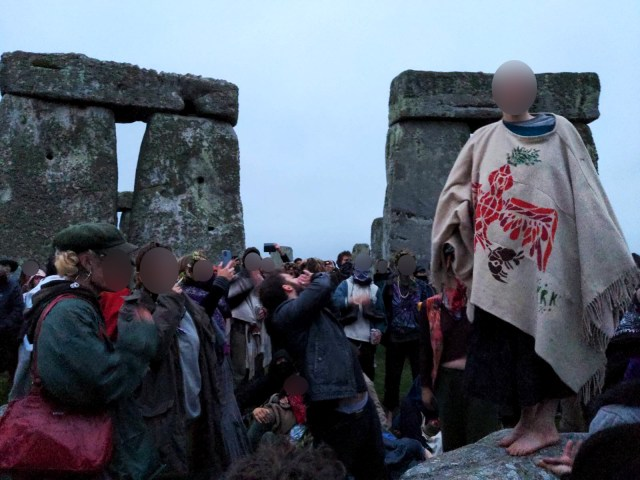 People gathering inside Stonehenge including one person wearing a ritual smock.