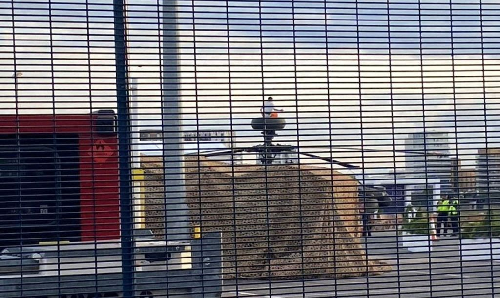 A protester against the DSEI arms fair sits atop a military helicopter behind a security fence
