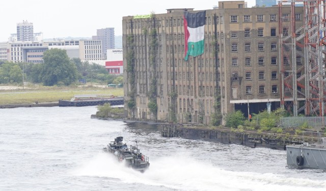 """A boat on the dock outside DSEI passes in fron of a disused building where a large Palestinian flag and an Extinction Rebellion banner saying """"Death Dealers - War Is Ecocide"""" has been dropped from the roof."""