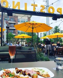 Photo of a yellow umbrella, wine, and food outdoors
