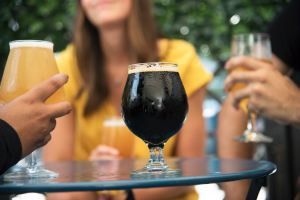 Image of table with dark beer and people