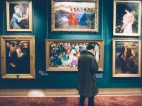 Image of a man in a coat standing in front of a museum gallery display with several paintings