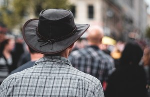 Image of man wearing a black cowboy hat with other people in the background