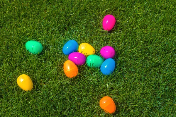 Brightly colored plastic Easter eggs on grass