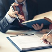 Businessman and Phoenix discuss a real estate lease & related contract documents.