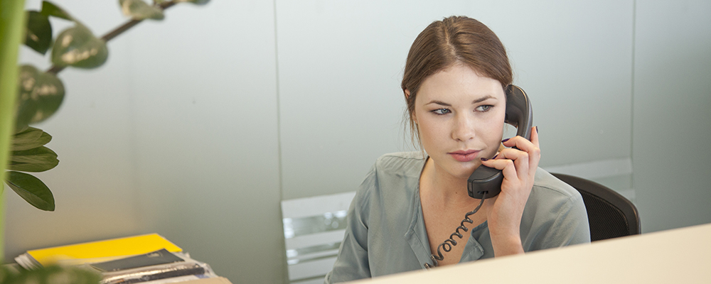 Young woman at front desk talking on the phone.