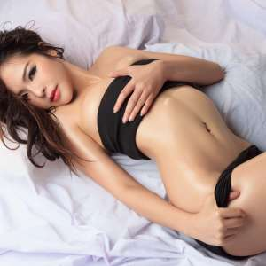 Sexy Asian woman lying on the bed