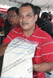 UDD co-leader Natthawut Saikua displays a bag of spoiled rice being provided to Thailand's rural poor by the Thai government
