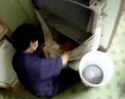 A worker filmed by 60 Minutes New Zealand hidden camera cleaning an air-conditioner in a fifth-floor room of The Downtown Inn, Chiang Mai.