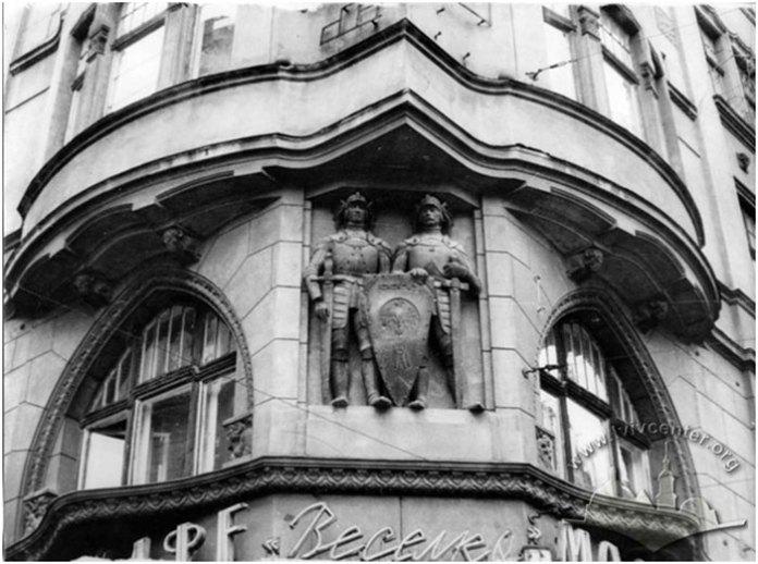 """Фотографія 1965 р., на якій зображено будинок № 12 (нині вул. Січових Стрільців). Зверху – фігури лицарів. Знизу – частково видно назву кафе """"Веселка"""" (на місці сучасної """"Пузатої хати"""")."""