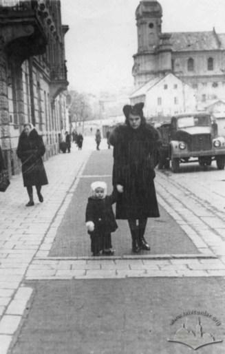 Жінка з дитиною на вул. Марченка (Тершаківців) на фоні костелу, в котрому на той час містився спортзал. Фото 1950-1955 рр.