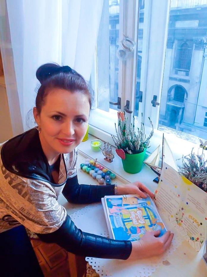 """Леся Кічура - співавтор та координатор проекту """"Щастя у віконці"""" з макетом омріяної книги в руках"""