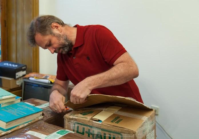 Голова ради Львівської обласної організації Українського товариства охорони пам'яток історії та культури Андрій Салюк відкриває першу коробку з книжками з Америки