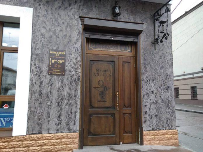 """Старі двері замінили на нові """"під старовину"""". над ними традиційна чаша і змія"""