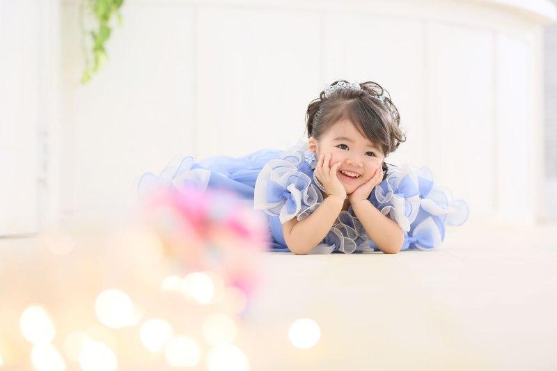 七五三の撮影で青いドレスを着てうつ伏せになっている女の子