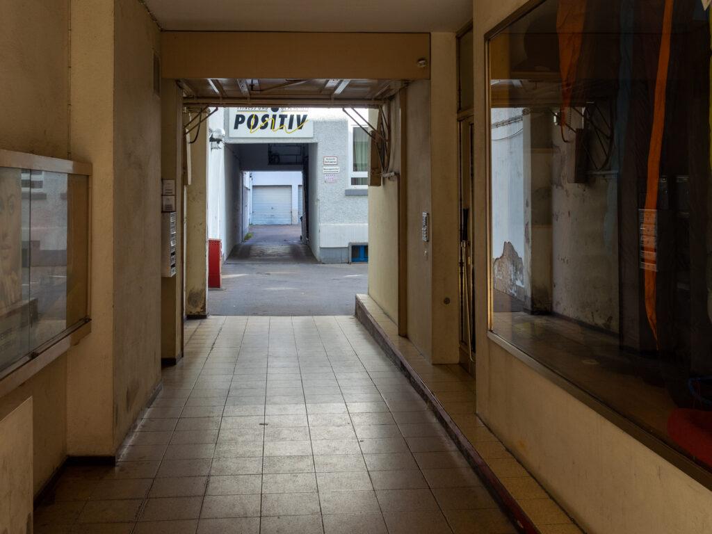 Das Bild zeigt eine Einfahrt mit gekacheltem Boden und dem Wort POSITIV im Hintergrund