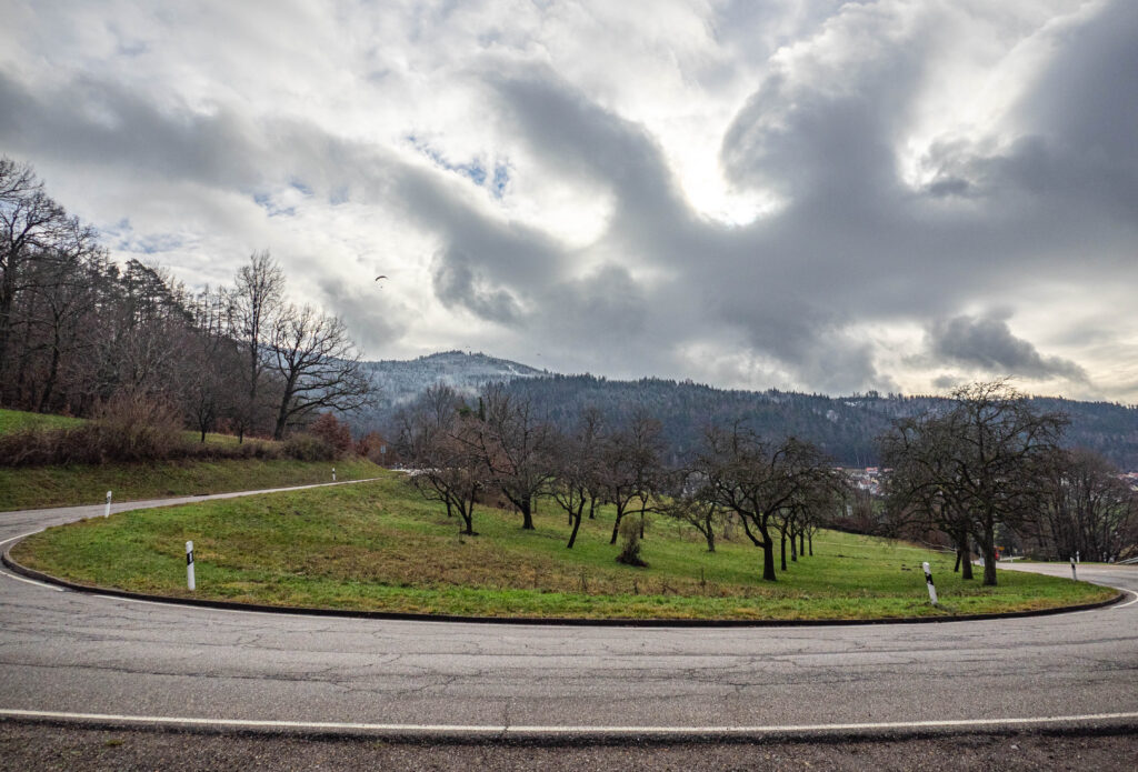 Das Bild zeigt eine Kehre einer Serpentinen starße im Schwarzwald mit Wolken im Hintergrund
