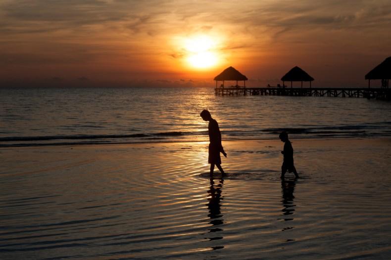 Silhouettes te réflexions de deux jeunes marchant dans l'eau au lever du soleil.