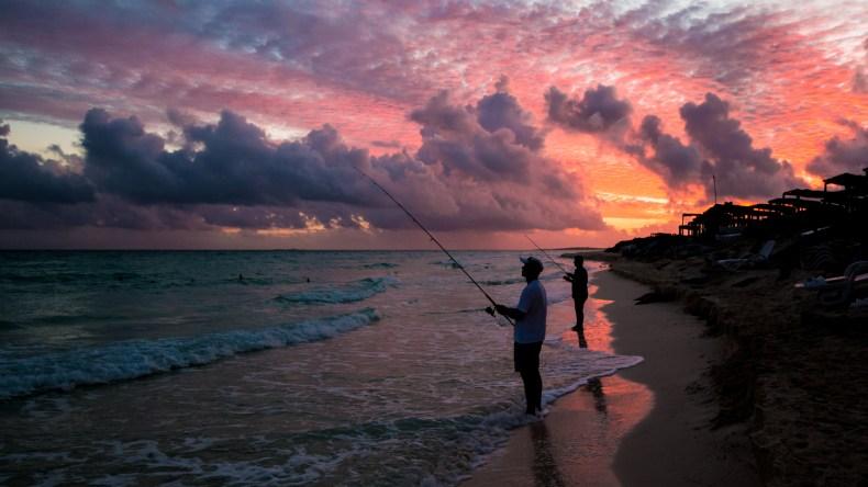 Silhouettes de pêcheurs avec un ciel rose orangé sur la plage