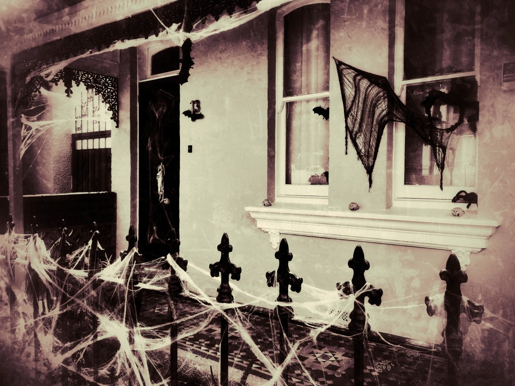 white town house with black fence and cobweb halloween decorations