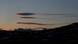The lenticular clouds are formed by a strong wind blowing a stable airmass over a tall obstacle (like a mountain chain). To paragliders they are a good indicator that the winds are now beyond safe, but to photographers they're just a great subject. These ones, with tails, are unlike any I have seen before.