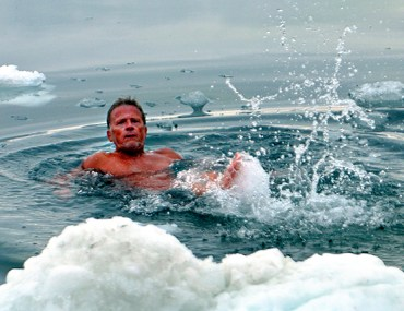 A man swims in freezing water in Ilulissat, Greenland, surrounded by icebergs.