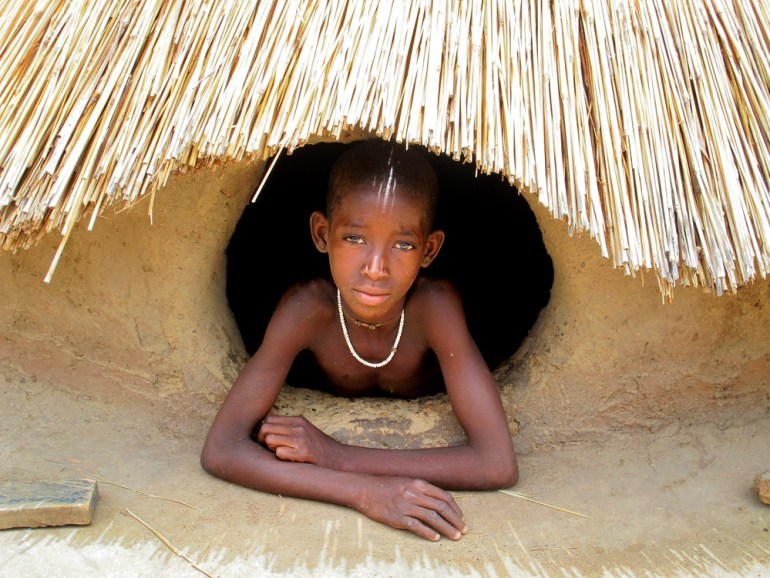 A Tamberma girl leans out of a window in her home in northern Togo.