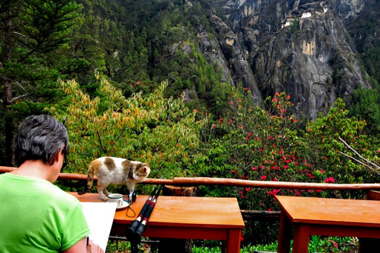 Woman drawing the Tiger's Nest Monastery in Bhutan with cat watching.