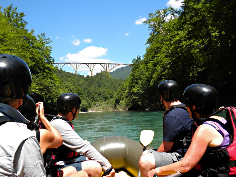 Group of people rafting on the Tara River in Montenegro while looking up at the bridge.