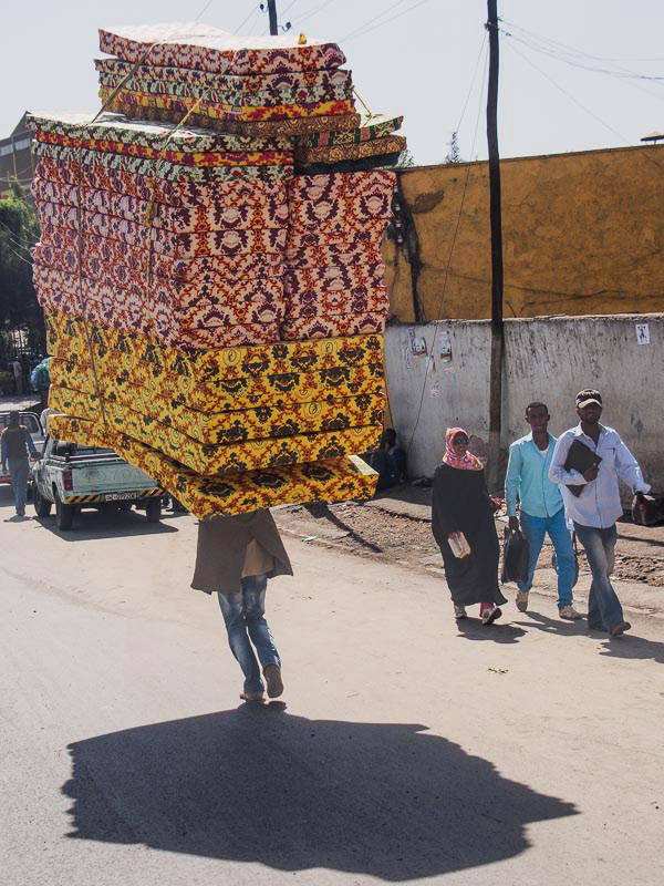 man carrying stack of mattresses
