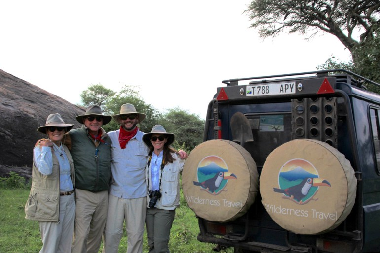 family on Serengeti with safari vehicle