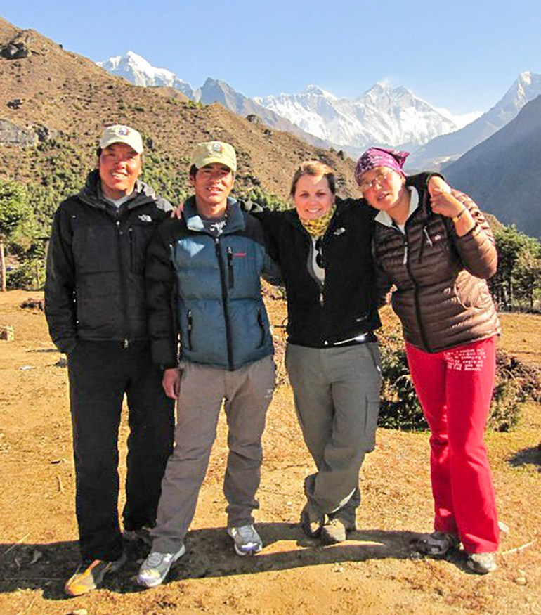 four people posing in front of the everest