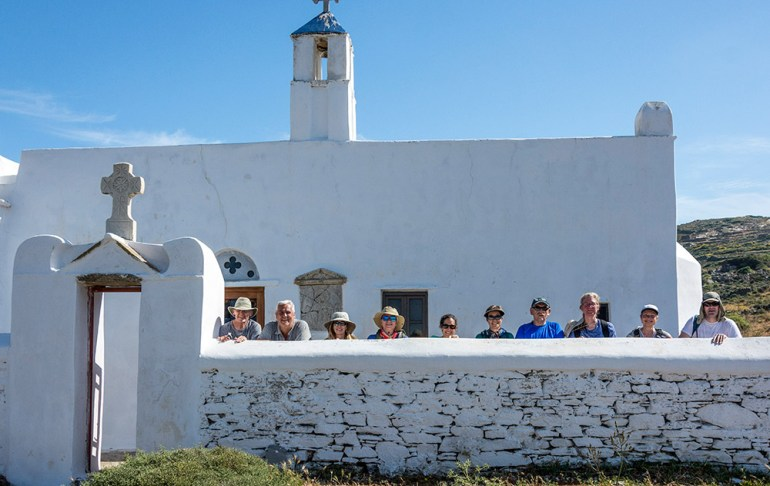 People in front of a small chapel in Tinos, Greece